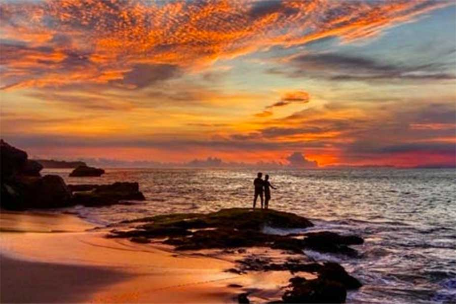 Two people on the beach at sunset