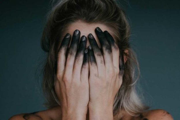 Girl with head in blackened hands